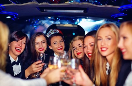 41066891 - group of happy elegant women clinking glasses in limousine hen party