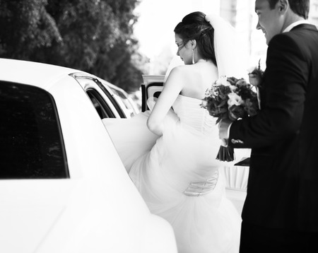 41568576 - young bride gets into limo. wedding couple.