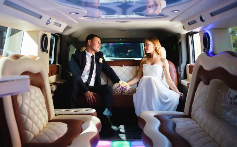 50655869 - happy bride and groom sitting in limousine