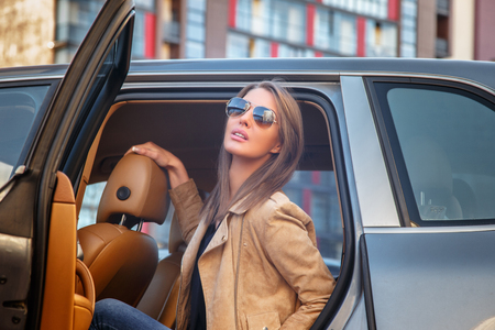 54571353 - casual young woman in sunglasses sits on a car's back seat.