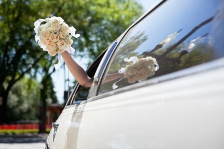 10723235 - bride waving hand from car holding flower bouquet