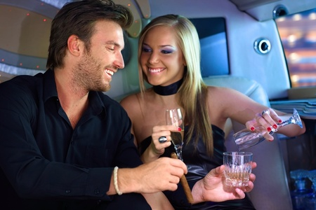 12070833 - attractive young couple having fun in limousine, drinking.