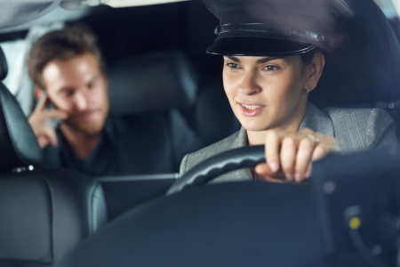 14767452 - female chauffeur driving a limousine, businessman in background.
