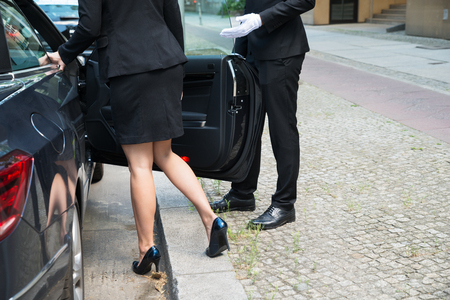 61416911 - male chauffeur opening the car door for the businesswoman on street