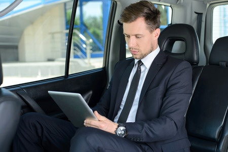28182969 - young successful businessman riding in the car