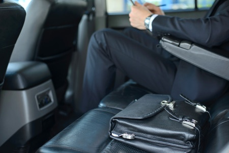 28182977 - young successful businessman riding in the car