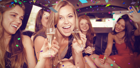 48575621 - flying colours against happy friends drinking champagne in limousine