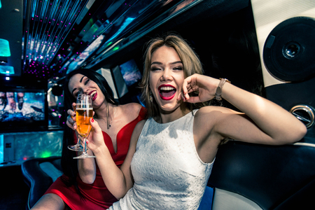 79816410 - pretty women having party in a limousine car